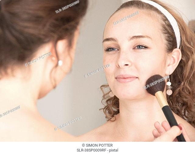 Teenage girl having her makeup done