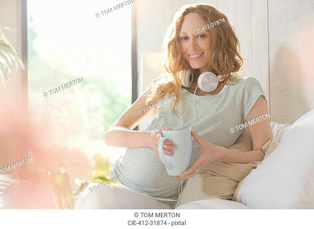 Portrait smiling pregnant woman with headphones drinking tea