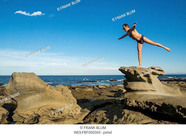 Australia, New South Wales, Tea Gardens, man on rock in yoga position