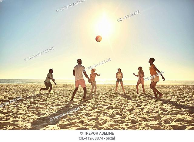 Young friends playing with beach ball on sunny summer beach