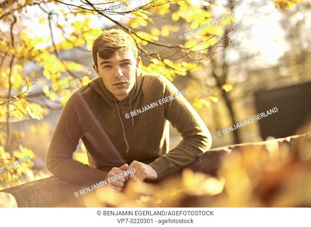 Young attentive man outdoors in autumn, in Munich, Germany