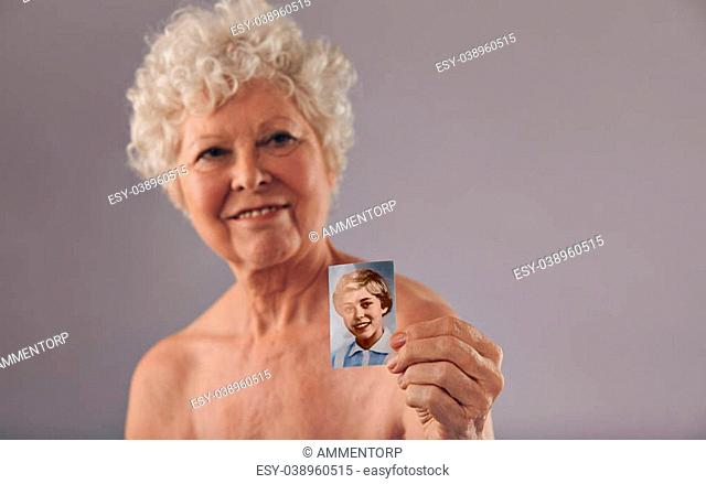 Portrait of a senior women holding her old photo. Beautiful woman shirtless showing a vintage photograph of her young age. Memory of her young days