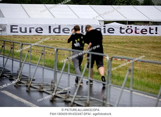 "09 June 2018, Germany, Themar: Festivalgoers at the right-wing festival """"Tage der nationalen Bewegung"""" walk past a banner that reads """"Eure Ideologie toetet"
