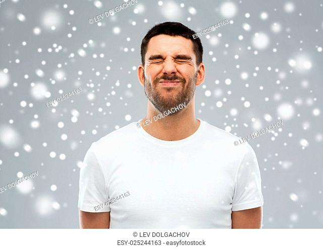 emotion, winter, christmas and people concept - young man screwing up his face over snow on gray background