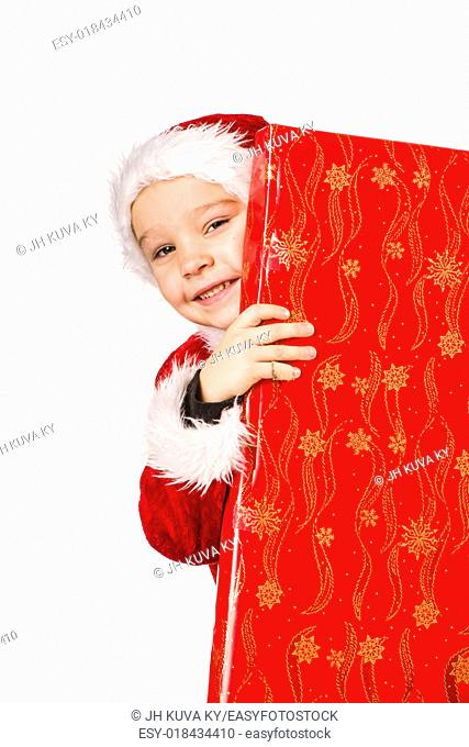 Smiling 5 year old boy wearing Santa Claus costume, Christmas gifts, white background