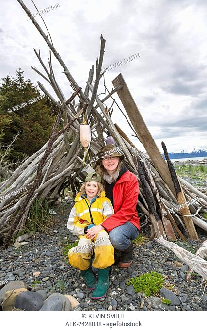 Mother and daughter pose in a driftwood shelter on Bishop's Beach, Homer, Southcentral Alaska, USA