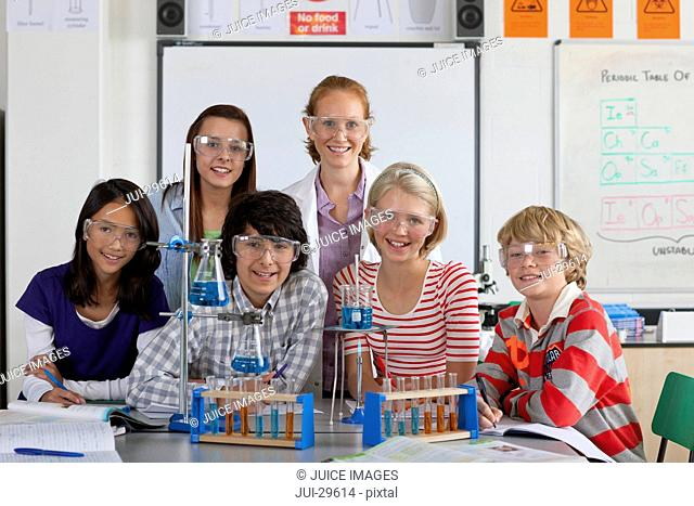 Teacher and students performing experiment in school chemistry laboratory