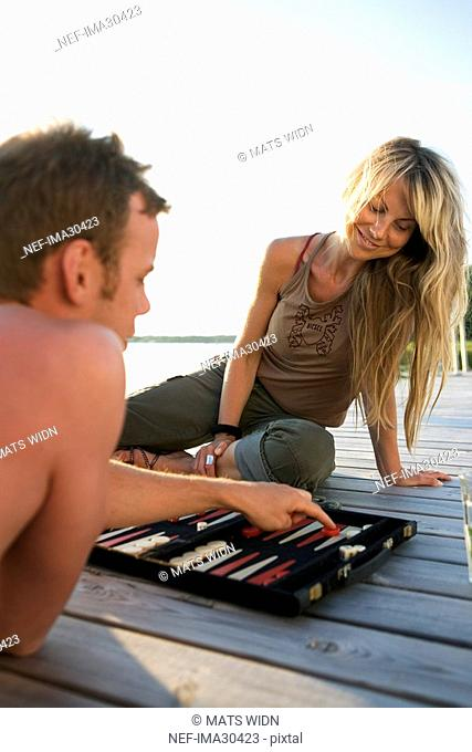 A man and a woman playing backgammon on a bridge