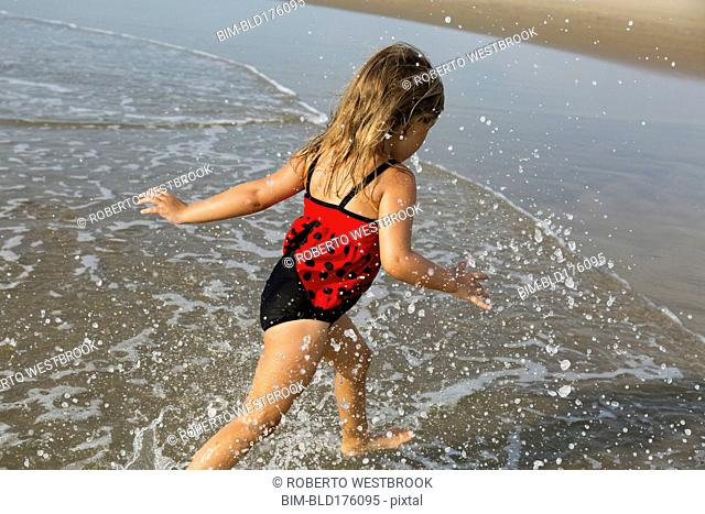Mixed race girl splashing in waves on beach