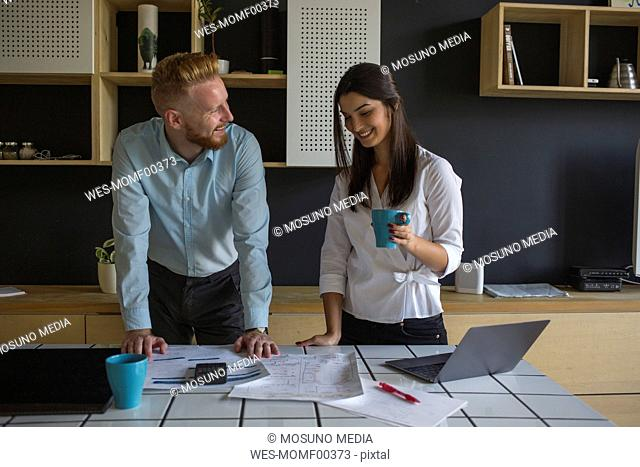 Smiling man and woman with plans on table at home