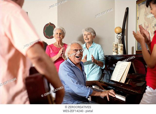 Elderly people making music in retirement home