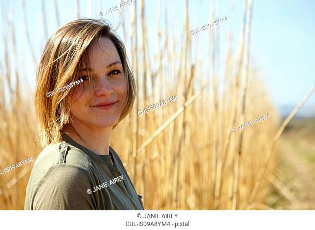 Portrait of young woman in front of reeds