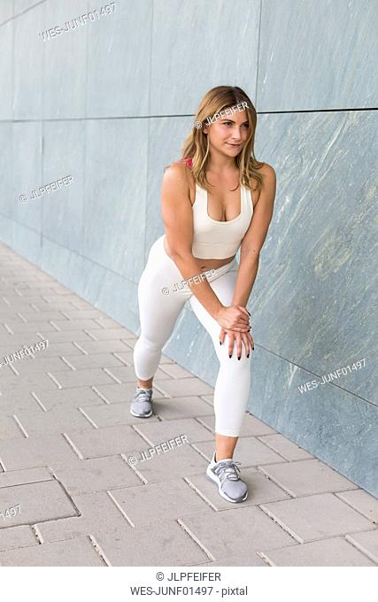 Portrait of smiling young woman dressed in white doing stretching exercises