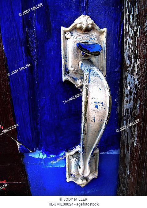 A silver door knocker on a blue door