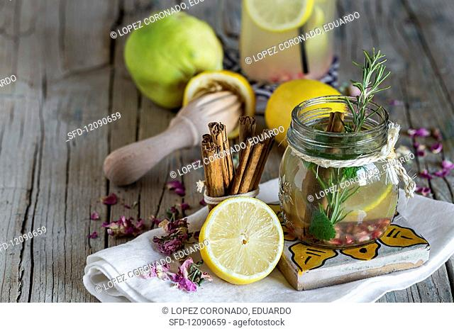 Lemonade with fresh lemon, mint, cinnamon and quince on a wooden surface