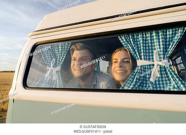 Happy young couple leaning against window of a camper van