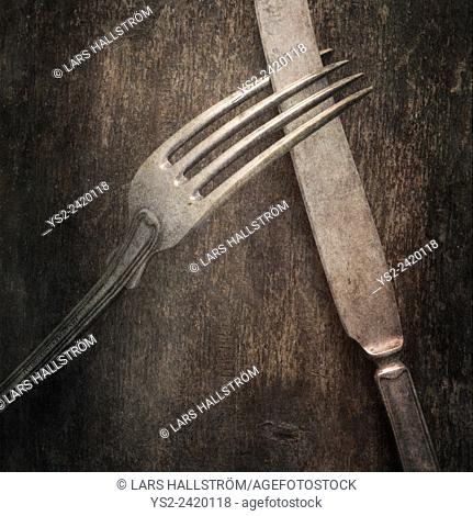 Still life with silverware on table. Knife and fork on a wooden background