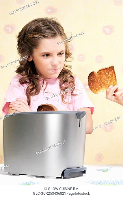 Woman giving her daughter a burnt toast