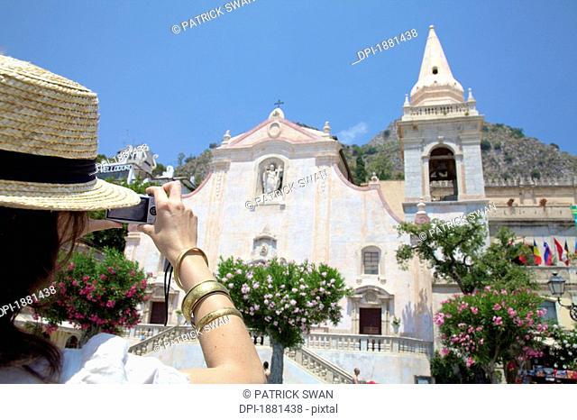 female tourist taking a picture of san giuseppe church, taormina, sicily, italy