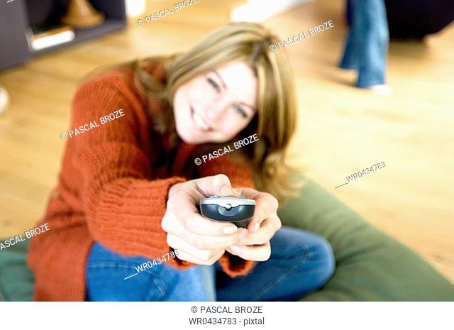 Portrait of a mid adult woman using a remote control