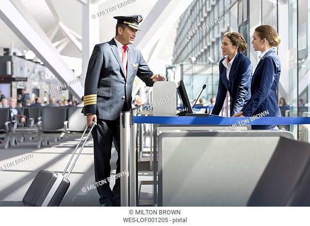 Pilot talking to stewardesses at boarding gate