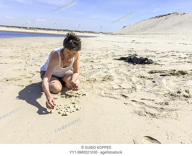 Maasvlakte, Rotterdam, Netherlands. Mature adult caucasian woman playing with washed ashore shells on an industrial beach during a sunny, summer day