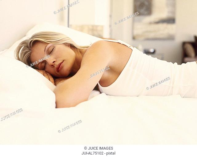 Portrait of a young woman sleeping on a bed