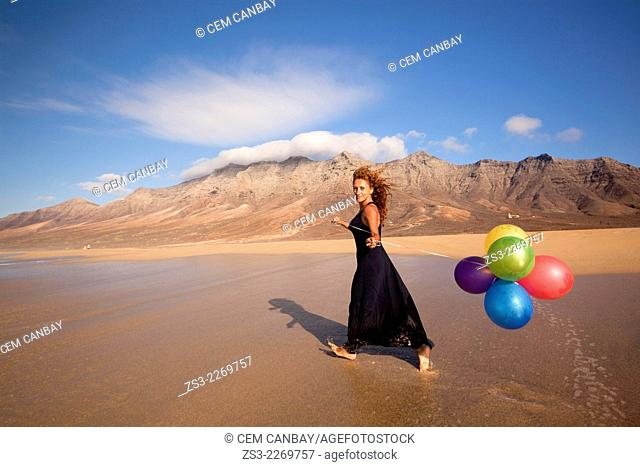 Woman with colorful balloons at Playa de Cofete beach, Fuerteventura, Canary Islands, Spain, Europe