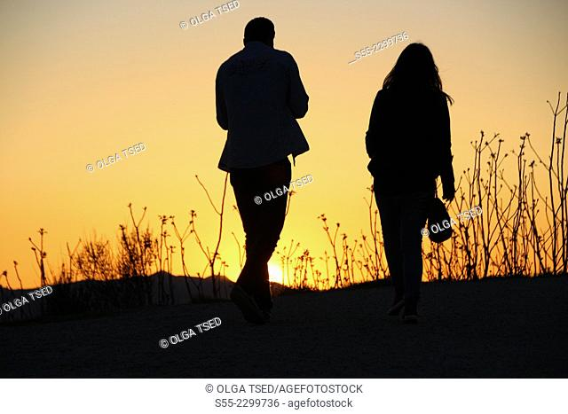 A young man and a woman walking in the sunset, Passeig de les Aigües; Collserola mountain, Barcelona, Catalonia, Spain