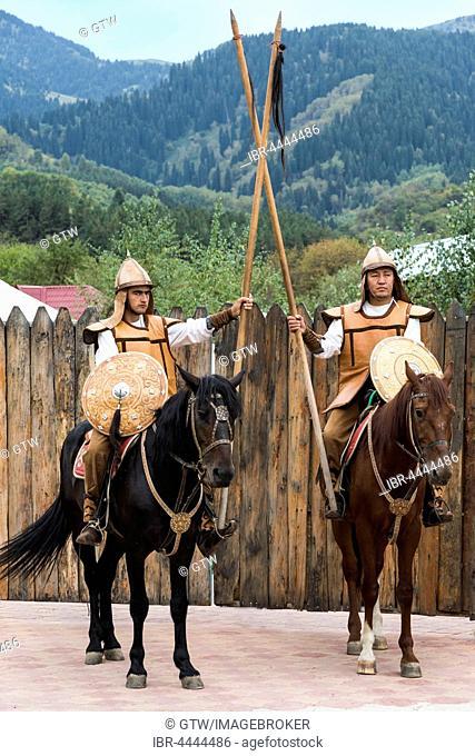 Two men on horseback in front of the entrance to the Kazakh ethnographic village aul Gunny, Talgar, Almaty, Kazakhstan