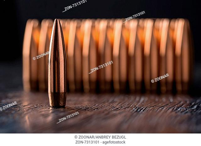 Macro shot of copper bullets that are in several rows on a black wooden background. One bullet stands alone