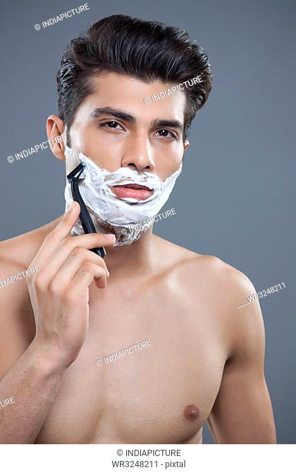 Portrait of young man shaving