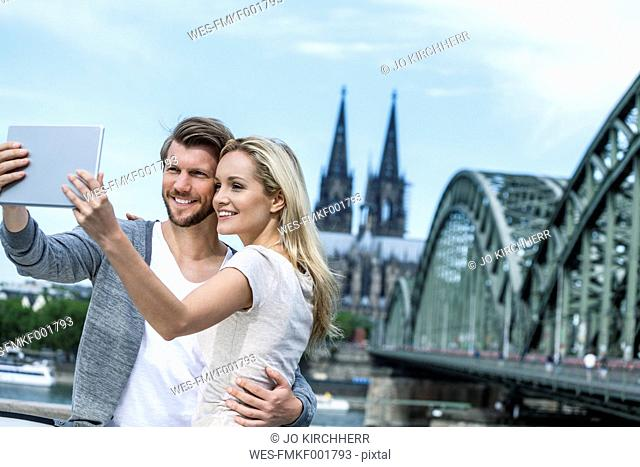 Germany, Cologne, smiling young couple taking a selfie with digital tablet