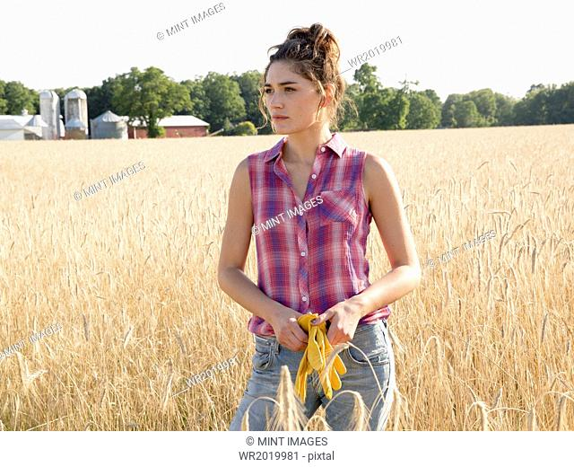 A young woman standing in a field of tall ripe corn