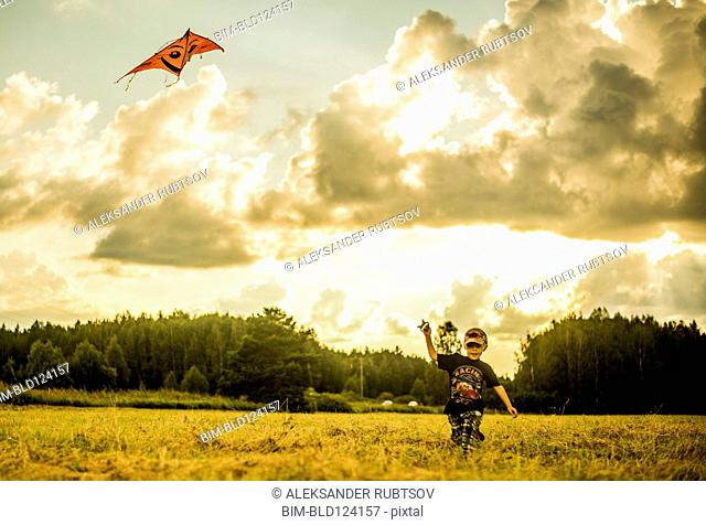 Caucasian boy flying kite in rural field