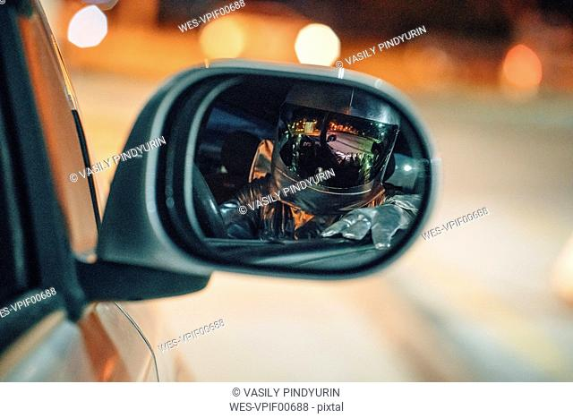 Reflection of spaceman in wing mirror of a car at night