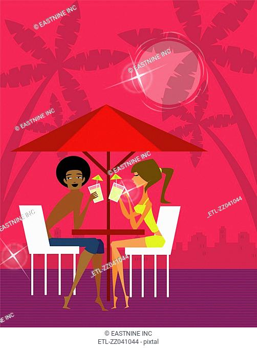 Side profile of a couple drinking juice under a sunshade