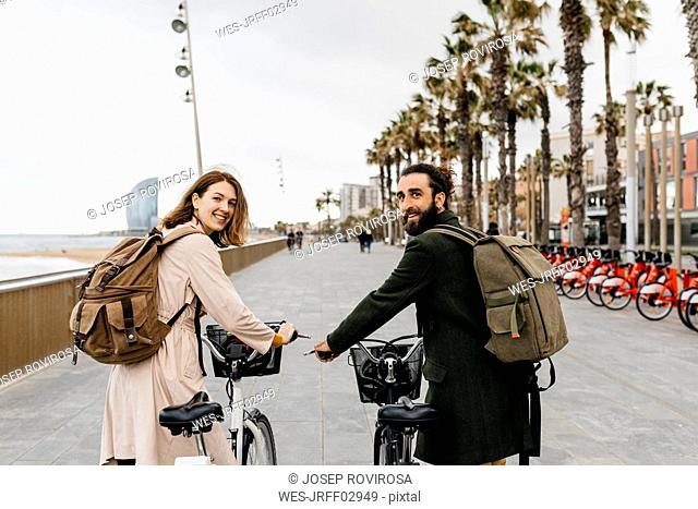 Smiling couple with e-bikes on beach promenade