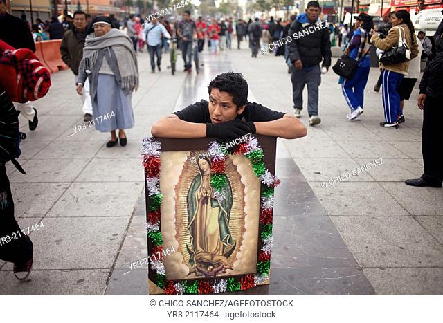 A man rests on an image of the Virgin of Guadalupe as he walks in his knees towards the Our Lady of Guadalupe Basilica in Mexico City, Mexico, December 11, 2013