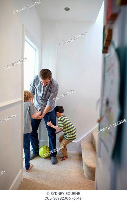 Mid adult man playing soccer with sons in hallway