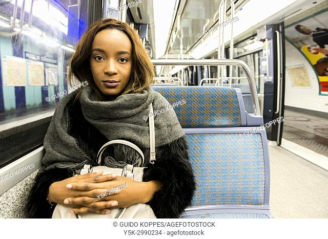 Paris, France. Urban portrait of a young adult, black woman and Sorbonne Law Student during a commute by subway, wearing modern fashion that defines her...