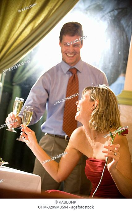Young couple in love toasting drinks at fine dining restaurant