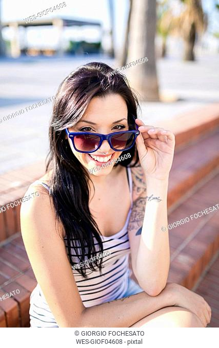 Portrait of laughing young woman with nose piercing and tattoos