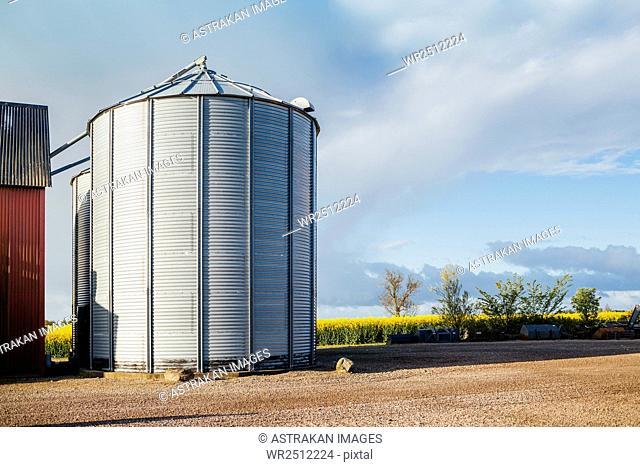 Storage tanks on field against sky