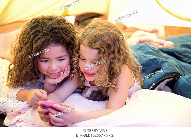 Girls using cell phone in camping tent