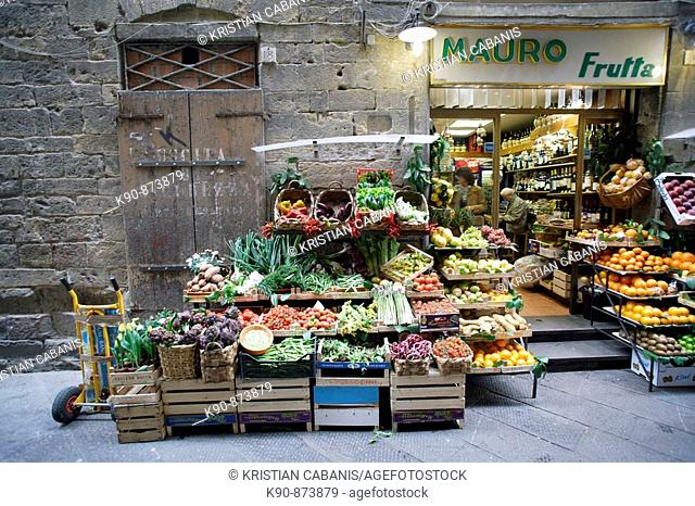 Traditional grocery store selling fruit and vegetable - and a pushcart besides - in a side street of the heart of Florence (Firenze), Tuscany, Italy