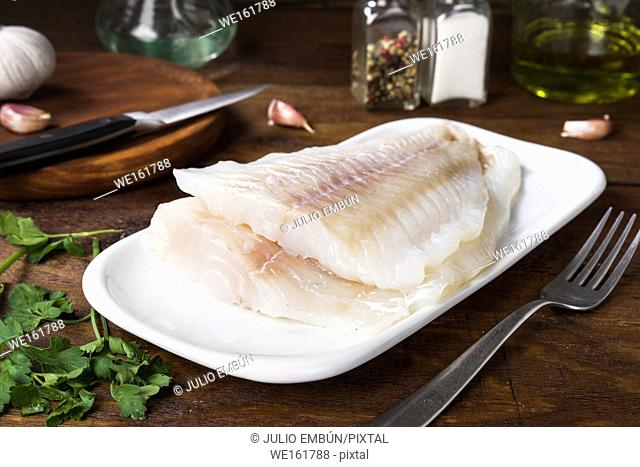 two fillets of fresh cod without cooking in rustic wood