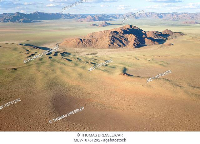 Aerial view of grass-grown sand dunes and isolated mountain ridges at the edge of the Namib Desert