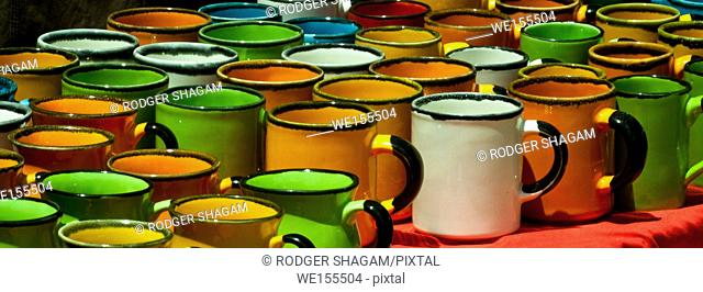 Enamel mugs in a variety of colors for a bright display at a flea market. Cape Town, South Africa