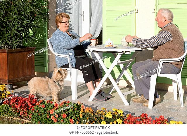 ELDERLY COUPLE WITH THEIR DOG ON THE HOME'S TERRACE, TOWN OF VERNEUIL-SUR-AVRE (27), FRANCE